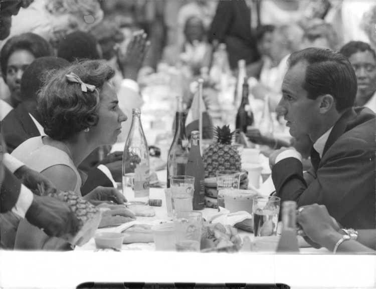 Aga Khan IV at a party with a table full of champagne and wine.