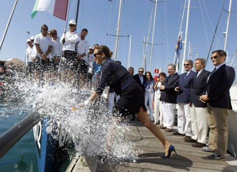 Zahra Aga Khan breaking a bottle of champagne on her boat's rudd.